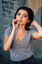 Portrait of white Caucasian beautiful young sexy brunette woman with light blue green eyes in jeans and t-shirt smoking Royalty Free Stock Photo