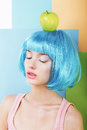 Portrait of woman in blue wig with green apple bizarre stylized Royalty Free Stock Photos
