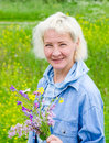 Portrait of woman with a bouquet of wild flowers middle aged Royalty Free Stock Photography