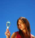 Portrait of woman with champagne outdoor head a young beautiful brunette caucasian toasting a full glass in front blue sky Royalty Free Stock Image