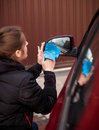 Portrait of woman cleaning car mirror closeup Stock Photo