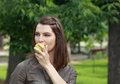 Portrait of a woman eating a green apple young biting in fresh outdoor in park Stock Photos