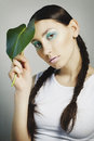 Portrait of woman with fashion make up with blue eye and leaf on Royalty Free Stock Photo