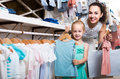 Portrait of  woman and girl shopping kids apparel in clothes sto Royalty Free Stock Photo