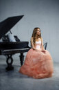 Portrait of woman with grand piano young caucasian in fluffy dress sitting at the Royalty Free Stock Photo