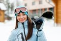 Portrait of woman handing skis wearing sports jacket and goggles who hands Royalty Free Stock Photos