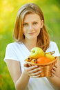 Portrait of woman holding basket with fruits young calm beautiful fair haired juicy at summer green park Royalty Free Stock Images