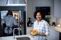 Portrait of woman holding bowl of salad while man opening a refrigerator in background Royalty Free Stock Photo