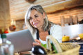 Portrait of woman in kitchen checking recipe on internet senior cooking with help tablet Royalty Free Stock Photos