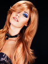 Portrait of a woman with long red hairs and fashion makeup beautiful blue eye on black background Royalty Free Stock Photo