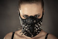 Portrait of a woman in a mask with spikes isolated on gray Stock Images