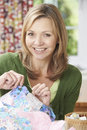 Portrait of woman sewing quilt at home enjoying Stock Image