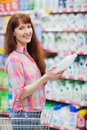 Portrait of woman with shopping basket holding detergent Royalty Free Stock Photo