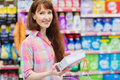 Portrait of woman with shopping basket holding product Royalty Free Stock Photo
