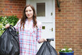 Portrait Of Woman Taking Out Garbage In Bags Royalty Free Stock Photo