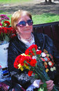 Portrait of a woman veteran with flowers war holds and smile victory day celebration on may in moscow Stock Image