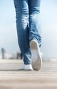 Portrait of a woman walking outdoors in comfortable white shoes close up Royalty Free Stock Image