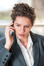 Portrait of worried looking business woman young while talking on mobile phone Royalty Free Stock Photography