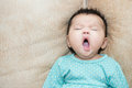 Portrait Of A Yawning Baby Gir...