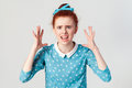 Portrait of young angry redhead girl in blue dress looking panic, screaming in camera with mouth wide open, with hands up. Royalty Free Stock Photo