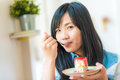 Portrait of young asian pretty smiling woman eating cake at cafe