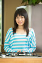 Portrait of a Young Asian woman in kitchen. Royalty Free Stock Photo