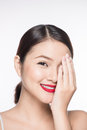 Portrait of young asian woman looking shy hiding behind her hand Royalty Free Stock Photo