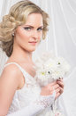 Portrait of a young and attractive blond bride beautiful standing in white dress holding flower bouquet the image is taken on Royalty Free Stock Photography