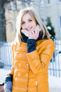 Portrait of young attractive blond woman in winter in the yellow jacket scarf happy smiling & looking at camera outdoor Royalty Free Stock Photo