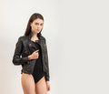 Portrait of a young attractive brunette woman posing for model tests in black leather jacket and body Royalty Free Stock Photo
