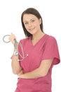Portrait of a young attractive female doctor with stethoscope beautiful gp general practitioner or nurse wearing pink theatre Stock Image