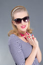 Portrait of young attractive pinup girl in sunglasses over grey Royalty Free Stock Images