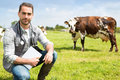 Portrait of a young attractive veterinary in a pasture with cows view Stock Photo