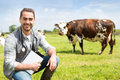Portrait of a young attractive veterinary in a pasture with cows view Stock Image