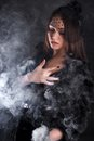Portrait of a young attractive woman in a puff of smoke Royalty Free Stock Photo