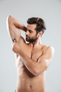 Portrait of a young bearded man shaving his armpit Royalty Free Stock Photo