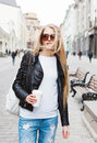 Portrait of a young beautiful blonde girl with sunglasses walking on the streets of Europe with coffee. The wind blowing her hairO Royalty Free Stock Photo