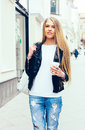 Portrait of a young beautiful blonde girl walking on the streets of Europe with coffee. Outdoor. Warm color. Royalty Free Stock Photo