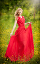 Portrait of young beautiful blonde woman wearing a long red elegant dress posing in a green meadow. Fashionable sexy attractive Royalty Free Stock Photo