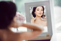 Portrait of the young beautiful bride looks at herself in the mirror Royalty Free Stock Photo