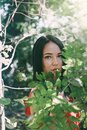Portrait of a young beautiful brunette woman among green lush foliage. Vertical orientation