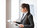 Portrait of young beautiful business woman reading documents in Royalty Free Stock Photo