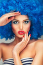 Portrait of a young beautiful girl with bright makeup in blue wi red lips wig Royalty Free Stock Photo