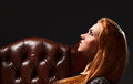 Portrait of the young beautiful girl in old leather armchair Stock Photography