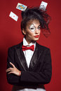 Portrait of a young beautiful lady croupier with playing cards an artistic make up joker and flying around on the red background Royalty Free Stock Photography