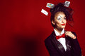 Portrait of a young beautiful lady croupier with playing cards an artistic make up joker and flying around on the red background Stock Photos
