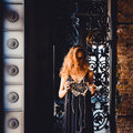 Portrait of young beautiful red-haired girl in the image of a Gothic witch on Halloween Royalty Free Stock Photo