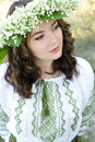 Portrait of a young beautiful in traditional Ukrainian embroidered shirt and a wreath of lilies of the valley Royalty Free Stock Photo