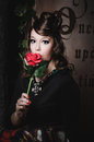 Portrait of young beautiful woman with funny expression and holding red roses around her face. Beauty fashion model girl Royalty Free Stock Photo
