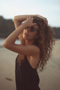 Portrait of a young beautiful woman with long curly hair in sunglasses Royalty Free Stock Photo